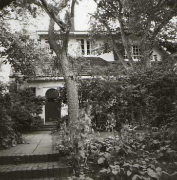 [a picture of the back of a house between trees and bushes]
