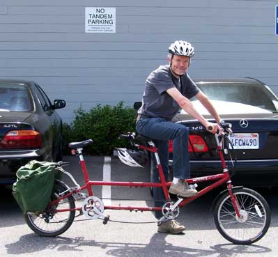[a picture of me on a tandem bicycle, waiting under a sign       'No Tandem Parking']
