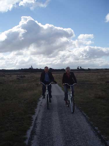 [two bicyclists sruggling against the wind, on a heath]