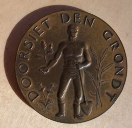 [medal showing a farm worker holding a shovel]
