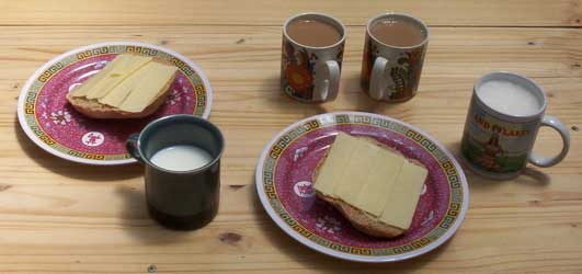 [lunch: slices of bread with cheese, milk, coffee]